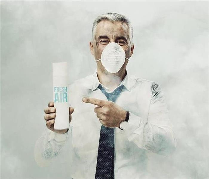 Man Holding Air Freshener while surrounded by Smoke